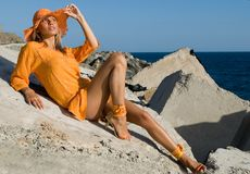 Woman with orange dress and hat Royalty Free Stock Images
