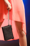 Woman in orange dress holds handbag, disco club Royalty Free Stock Photography