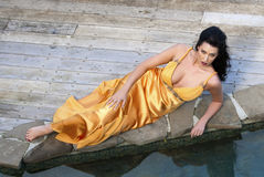 Woman in an orange dress laying by the pool Royalty Free Stock Image