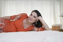 Woman In Orange Dress Lying In Bed Royalty Free Stock Image
