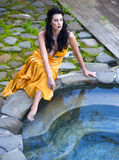 Woman in an orange dress sitting by the pool Royalty Free Stock Images