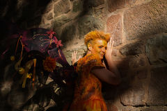 Woman in orange fairy costume leaning against castle wall stock photo