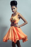 Woman in orange flared dress. Elegant, glamorous fashion model showing off  a designer orange dress with lacy top, decorated middle and flared skirt  made with Royalty Free Stock Photography