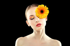 Woman with an orange flower. Woman with an orange flower on her face Stock Photo