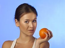 The woman with an orange fruit Royalty Free Stock Photography