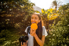 Woman with orange in the garden. Happy woman holding orange fruit in the tropical garden royalty free stock photography