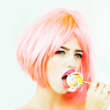 Woman with orange hair lick lollipop. Young sexy woman with bright makeup on pretty face and orange hair lick lollipop candy on white background Royalty Free Stock Photography