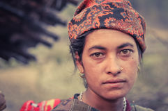 Woman with orange headcloth in Nepal. Dolpo, Nepal - circa May 2012: Native woman with piercing and earrings wears orange headcloth with brown eyes in Dolpo Stock Photo