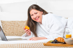 Woman with orange in her hand on the bed Stock Photos