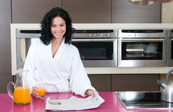 Woman with orange juice at domestic kitchen Stock Photos