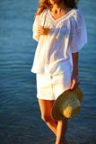 Woman with orange juice and a hat in hand against the sea Stock Photos