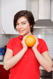 Woman with orange in kitchen Stock Photo