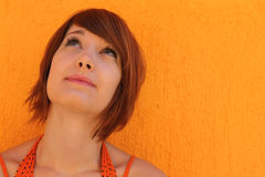 Woman in orange looking up Stock Photo