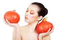 Woman with orange make up holding pumpkin Royalty Free Stock Image