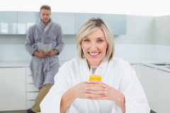 Woman with orange and man reading newspaper in kitchen Stock Image