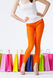 Woman in orange pants and multicolored shopping bags Royalty Free Stock Photography