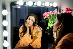 Woman in orange robe doing her makeup and wathching in mirror Royalty Free Stock Images