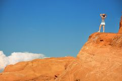 Woman on orange rock Stock Images