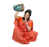 Woman in orange sari sitting and holds turban Royalty Free Stock Photography