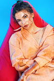 Woman in orange shirt lying on red chair on blue background Royalty Free Stock Photos