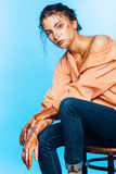 Woman in orange shirt sitting on chair on light blue background Royalty Free Stock Photography