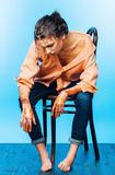 Woman in orange shirt sitting and jeans sitting on wooden chair Stock Photo