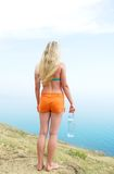 Woman in the orange shorts. Young woman in the orange shorts standing on the beach with a bottle of water Royalty Free Stock Photo
