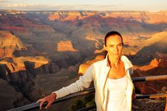 Woman in orange sunset at the Grand Canyon Stock Photo