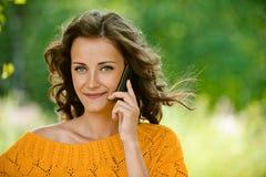 Woman in orange sweater talking on Stock Photos