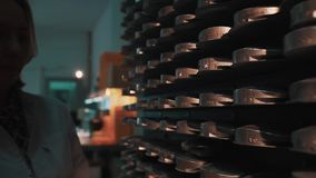Woman with orange tray walks to shelves with stacks of metal discs. Caucasian woman in white robe with orange tray walks to shelves with stacks of metal discs at stock video footage