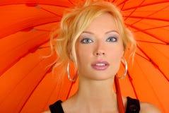 Woman with orange umbrella Stock Photos