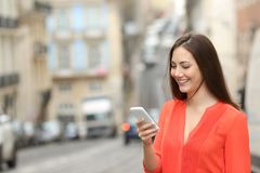 Woman in orange uses a smart phone in the street. Happy woman in orange uses a smart phone walking in the street Royalty Free Stock Photos