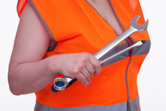 Woman in orange vest holds tools in hand Royalty Free Stock Photo
