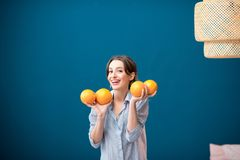 Woman with oranges on the blue background Stock Images