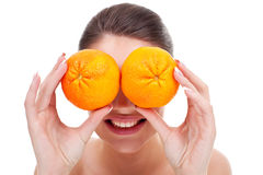 Woman with oranges in her hands. Young woman with oranges in her hands , over eyes, on white background Royalty Free Stock Image
