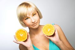 Woman with oranges. Young blonde woman with oranges in her hands Royalty Free Stock Photos