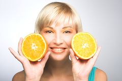 Woman with oranges. Young blonde woman with oranges in her hands Stock Photography