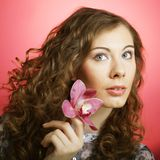 Woman with orchid flower over pink background Royalty Free Stock Images