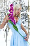 Woman with orchid in the winter forest Royalty Free Stock Photography