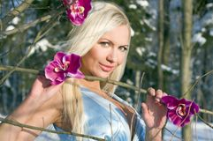 Woman with orchid in the winter forest Royalty Free Stock Photo