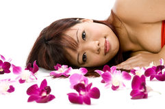 Woman with Orchids. A young Asian woman lying on the floor with purple orchid flowers Royalty Free Stock Image