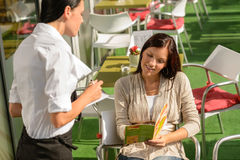 Woman order from waitress at cafe terrace. Woman deciding order from waitress at cafe terrace looking menu Royalty Free Stock Images