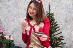 Woman ordering gift on internet. female buyer holding smartphone. For online shopping. girl use credit card for payment. christmas holiday. merry xmas Royalty Free Stock Photo