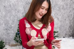 Woman ordering gift on internet. female buyer holding smartphone. For online shopping. girl use credit card for payment. christmas holiday. merry xmas Royalty Free Stock Photography