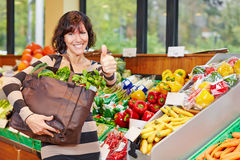 Woman in organic food store holding Stock Photos