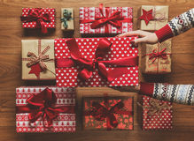 Woman organising beautifully wrapped vintage christmas presents on wooden background, image with haze. View from above Royalty Free Stock Image