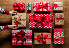 Woman organising beautifuly wrapped vintage christmas presents on wooden background Stock Photos