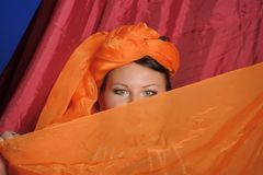 Woman in oriental clothes covering her face royalty free stock photo