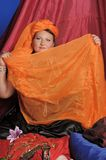 Woman in oriental clothes covering her face stock images