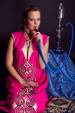 Woman in oriental outfit smoking water-pipe Stock Image